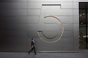 A businessman walks beneath a large number five outside corporate offices, on 9th December 2016, in the City of London.