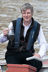 Zac Goldsmith MP introducing 10,000 eels into the River Thames. Zac Goldsmith MP (R) and Andrew Kerr (L) Chairman of Sustainable Eel Group, talk with a jar full of eels before release several thousands eels from a boat into the Thames in front of the Houses of Parliament to publicise conservation mission to relocate more than 90 million critically endangered European eels. River Thames, Westminster, United Kingdom. Monday, 19th May 2014. Picture by Daniel Leal-Olivas / i-Images