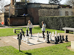 © Licensed to London News Pictures. 07/04/2015. London, UK. Two girls play outdoor chess in the sunshine and warm spring weather in Holland Park in west London this morning. Photo credit : Vickie Flores/LNP
