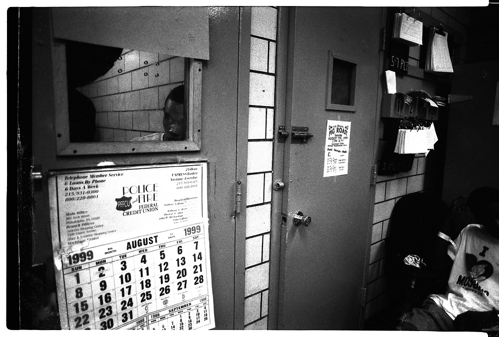 Two young men peer out of a jail cell at the 18th district in Philadelphia
