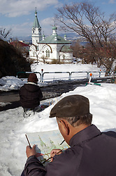 Man painting former Russian Orthodox church in Hakodate Hokkaido Japan