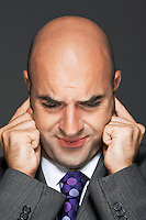 Bald businessman with fingers in ears making a face