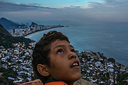 Rio de Janeiro, Brazil - June 15, 2013: A boy flies a kyte atop of a boutique hotel under construction at Vidigal hillside slum as Ipanema beach appears in the background. As cries of price gouging intensify just six months ahead of the start of the World Cup, with even modest hostels in Rio de Janeiro charging as much as $450 for a bed during the soccer tournament, the dwellers of Rocinha and other favelas are offering their own solution to Rio's acute shortage of hotel rooms: renting out their homes to soccer fans seeking a place to stay. CREDIT: Photo by Mauricio Lima for The New York Times