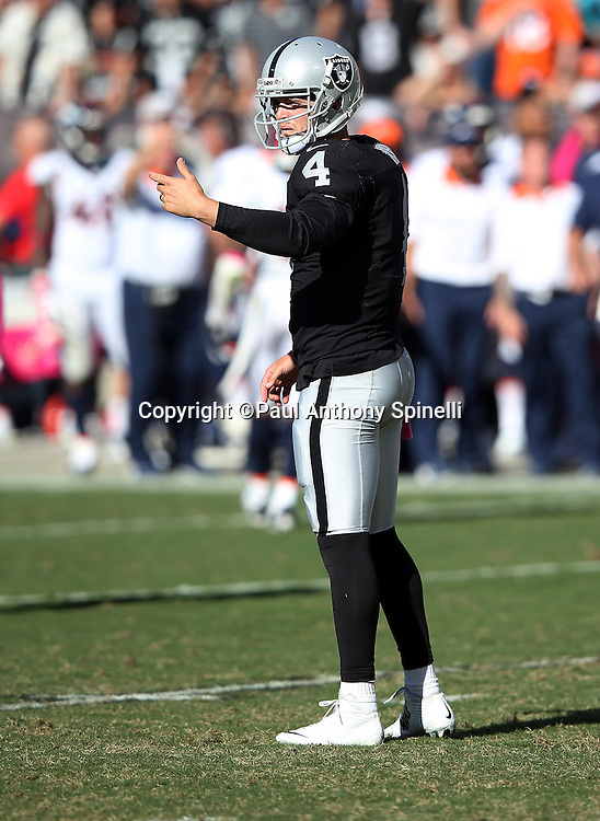 Oakland Raiders quarterback Derek Carr (4) motions toward the sideline during the 2015 NFL week 5 regular season football game against the Denver Broncos on Sunday, Oct. 11, 2015 in Oakland, Calif. The Broncos won the game 16-10. (©Paul Anthony Spinelli)