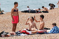 © Licensed to London News Pictures. 12/07/2014. Brighton, UK. People sunbathing and having fun on Brighton Beach. With temperatures around the 23C down the South Coast thousands of people taking a weekend away down on the beach. Photo credit : Hugo Michiels/LNP