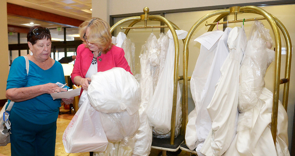 gbs072717c/ASEC -- Loretta Carter of Albuquerque, left gives her daughter's wedding dresses to Catherine Hatcher with the Albuquerque Marriott Pyramid North, as part of the bridal dress drive for women left out in the cold by the closing of Alfred Angelo bridal shop on Thursday, July 27, 2017. (Greg Sorber/Albuquerque Journal)
