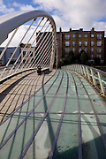 The bridge is designed by Spanish architect Santiago Calatrava, and is a single-span structural steel design,reaching from Blackhall Place to the South Quays, near the James Joyce house, at 15 Usher's Island, featured in the book, the Dead. The house is the one in the background of the image..