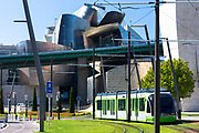 Modern tram passes traffic lights and Guggenheim Museum in Bilbao in Basque country, Spain