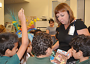Piney Point ES Principal Swaby talks with students about the books they chose at the Books Between Kids give-away celebration.