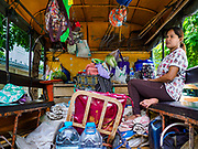 11 JULY 2017 - BANGKOK, THAILAND: A woman who used to live in the Khiao Khai Ka community sits in the back of a city of Bangkok truck with her belongings. Her home was torn down by the city. Bangkok city workers cleared 20 homes from the Khiao Khai Ka community along the Chao Phraya River. The community is the first to be evicted as the city goes ahead with its plan to build a 14 kilometer long (22 mile) riverfront promenade. Thousands of families are expected to be evicted to make way for the promenade. Residents in the Khiao Khai Ka community agreed to leave voluntarily and will receive compensation for their homes. The exact amount of the compensation has not been determined.      PHOTO BY JACK KURTZ