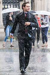 London, UK. 6 June, 2019. A man seeks shelter outside the Palace of Westminster during a sudden rain shower. Scattered showers are forecast for the remainder of the day, with heavy rain to follow tomorrow.