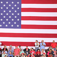 Supporters begin to stand against the backdrop of a large American flag before President Donald Trump takes the stage Tuesday night.