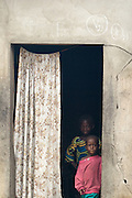 Children stand in a doorway in the village of Lalo, Benin on Tuesday September 18, 2007. The chalk marks above the door indicate that children have been vaccinated.