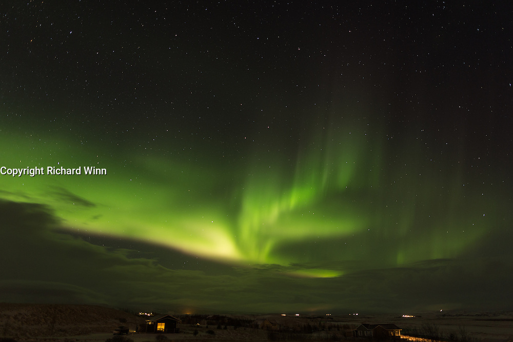 Aurora Borealis over Eyjasol cottages, with some cottages in the foreground.