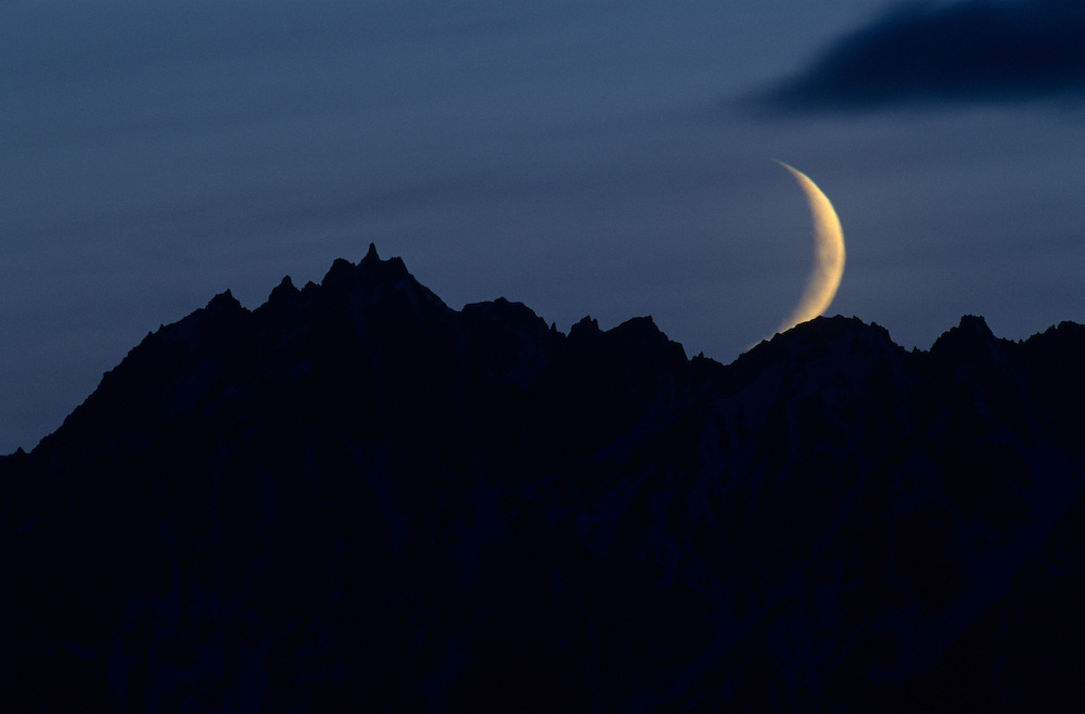 USA, Alaska, Denali National Park, Crescent moon sets behind Alaska Range peaks above Chulitna River