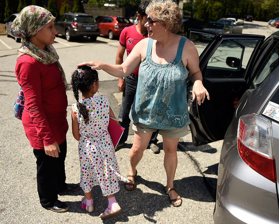 1005612433 :: 7/27/16 :: REGION :: LYNCH :: Ledyard Congregational Church member Deb Betz greets Fahima Jemmo, left, her husband, Hasan Mahmoud, back, and daughter Fulla, 7,  as she arrives to take them to their next destination after attending English for Speakers of Other Languages class at New London Adult and Continuing Education Wednesday, July 27, 2016. Hasan Mahmoud and Fahima Jemmo and their children Fidan, 17, Hanif, 15 and Fulla, 7, are refugees from the conflict in Syria and lived for three years in Turkey before finally receiving approval to come to the United States. (Sean D. Elliot/The Day)
