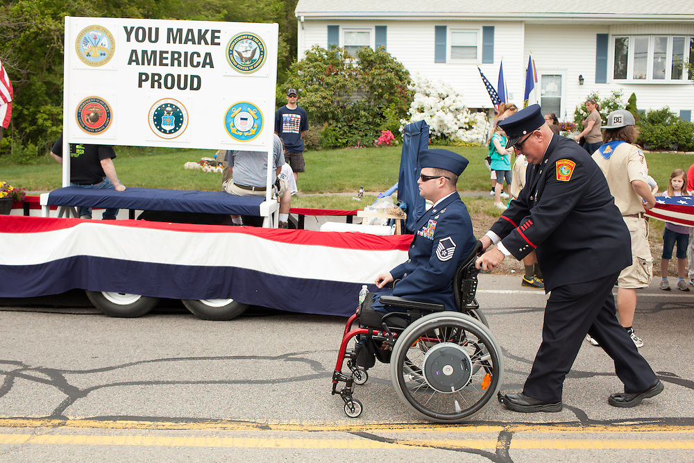 Injured Air Force Master Sgt. Joseph Deslauriers Jr. is pushed by his father Joseph Sr. before the start of a Memorial Day parade where he served as grand marshall in his home town of Bellingham, MA on Sunday, May 19, 2013. The parade was held a week before the holiday to ensure greater attendance. In 2011, Deslauriers lost both of his legs and part of an arm after stepping on an explosive device while stationed in Afghanistan. He is currently rehabbing at Walter Reed Army Medical Center.  (Matthew Cavanaugh for The Washington Post)