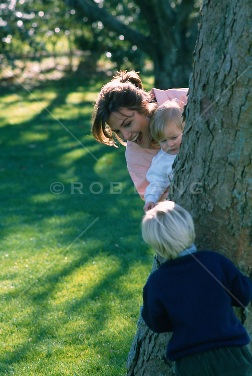 woman playing hide and seek with little boy and baby