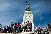 LESVOS, GREECE - NOV 6: Refugees gather around the Statue of Liberty at the port of Mytilene, Lesbos to commemorate the lives of the thousands of people who have drowned in the Aegean Sea trying to reach the safety of European shores.