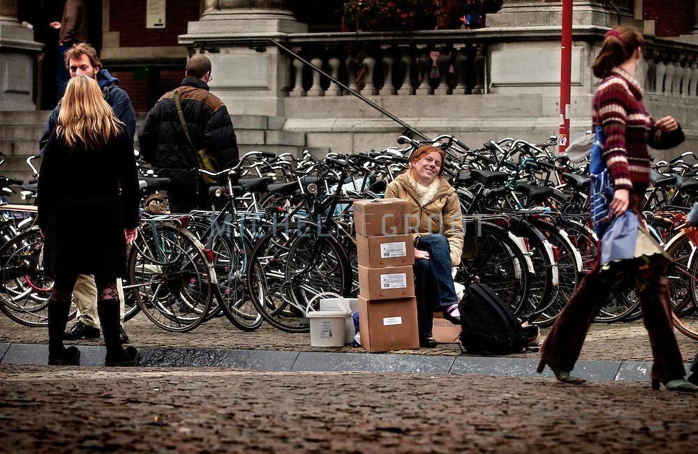 GRONINGEN, Netherlands - 8-11-2004: EKO PATAT ACTIE SMOG EN DWARS. Leentje Haaksma zit gelaten te wachten op het Academieplein met 40 kilo friet in dozen. De actie viel in het water omdat de frietkraam niet kwam opdagen.