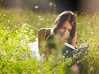 Young woman lying in meadow reading book