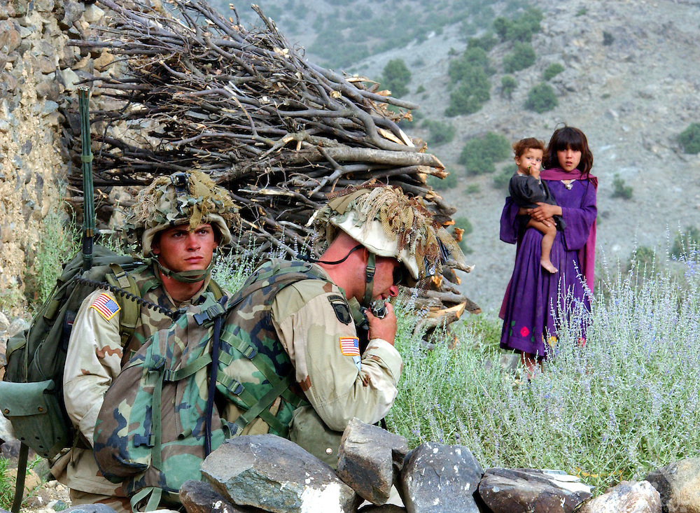 """Afghan girls watch as US Army 101st Airborne 3-187 """"Bravo"""" company soldiers radio their position during a 23 July, 2002 sensitive site exploitation (SSE) mission in the town of Narizah in Southeastern Afghanistan . The three day mission, intended to deny sanctuary to Al Qaida and Taliban fighters in villages along the Pakistan-Afghanistan border resulted in the recovery of several weapons caches and one Afghan detained for questioning."""