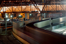 Freight trains in motion behind Union Station in downtown Kansas City, Missouri at dusk.