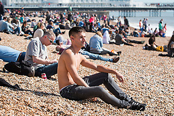© Licensed to London News Pictures. 25/03/2016. Brighton, UK.  A man sunbathing topless as Thousands of people relax in the sun on Brighton Beach at the start of the Easter Bank Holliday weekend. Photo credit: Hugo Michiels/LNP