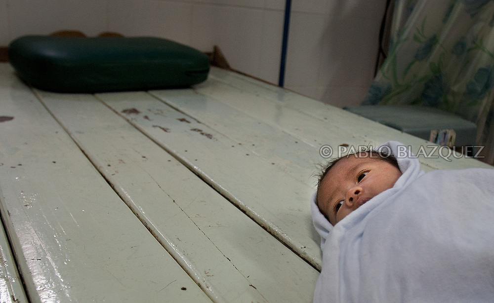 A new born baby lays on a bed at Mae Tao Clinic, on December 20 of 2006, in Mae Sot area, Thailand..The Mae Tao Clinic was founded on 1988 by Dr. Cynthia Maung and gives medical care for migrant and refugees, fleeing Burma, in the Mae Sot area, Thailand..Burma has since 1962 been ruled by dictator Burman Regimes. Pro democrats and minority ethnics have since been object of human rights abuses and armed minority groups has appeared, bringing a state of Civil War..This has forced Burmese people to flee their villages and on their arrival to Thailand many suffer from malnutrition, illnesses and injuries, amputations from land-mines or traumas. The Mae Tao Clinic supported by donors and volunteers provides with free health care and treatment to these people.
