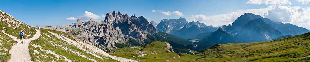 "The peaks of Cadini Group, Sorapiss Group, and Monte Cristallo rise (left to right) in the Dolomites, Veneto region, Italy, Europe. In the Cadini di Misurina, Cima Grande rises to 2999 meters (9839 feet), between Cima Piccola and Cima Ovest. Sorapiss and Monte Cristallo are in the Ampezzo Dolomites. The Cadini Group is in the Sesto Dolomites (Dolomiti di Sesto, or Sexten/Sextner/Sextener Dolomiten) which lie north of the Fiume Ansiei valley and Auronzo. From the Rifugio Auronzo toll road, hike for spectacular views around Tre Cime di Lavaredo (Italian for ""Three Peaks of Lavaredo,"" called Drei Zinnen or ""Three Merlons"" in German). The Dolomites are part of the Southern Limestone Alps. UNESCO honored the Dolomites as a natural World Heritage Site in 2009. Panorama stitched from 8 overlapping photos."