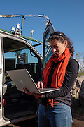 Gabrielle Pétron, a climate scientist from the University of Colorado Boulder, working in NOAA's Earth System Research Laboratory, uses equipment in NOAA's mobile lab to check area methane levels in real time.