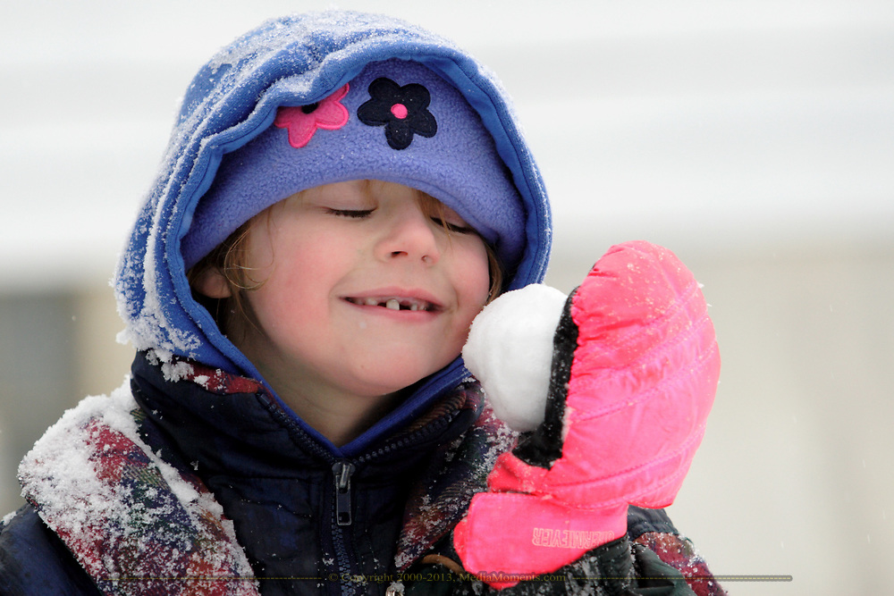 Destiny Richardson, 6, of Dayton, holds a snowball to her cheek Tuesday during the Winter storm.