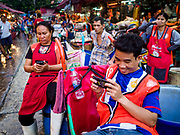 "04 DECEMBER 2018 - BANGKOK, THAILAND: Porters check their smart phones while they wait for customers in Khlong Toei market.  Khlong Toey (also called Khlong Toei) Market is one of the largest ""wet markets"" in Thailand. The market is located in the midst of one of Bangkok's largest slum areas and close to the city's original deep water port. Thousands of people live in the neighboring slum area. Thousands more shop in the sprawling market for fresh fruits and vegetables as well meat, fish and poultry.     PHOTO BY JACK KURTZ"