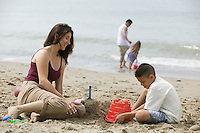 Mother building sandcastles with son on beach
