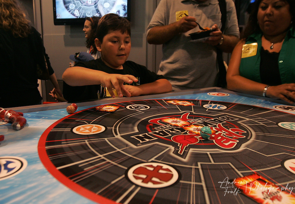 "/Andrew Foulk/ For The North County Times/.Trevor Sullivan, 10, of Santee, gets a lesson on how to play ""Bakugan"" a dice and card game, during preview night at the 40th annual San Diego Comic Con International."