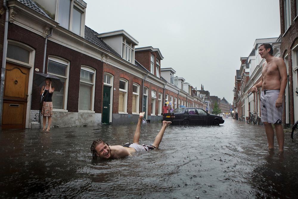 A huge downpoar has caused several streets to flood in the city of Groningen. Some students are enjoying the temporary pool // Door een enorme  regenbui zijn in Groningen enkele straten overgelopen. In de Nieuwe St Jansstraat hebben een paar studenten lol met een surfplank.