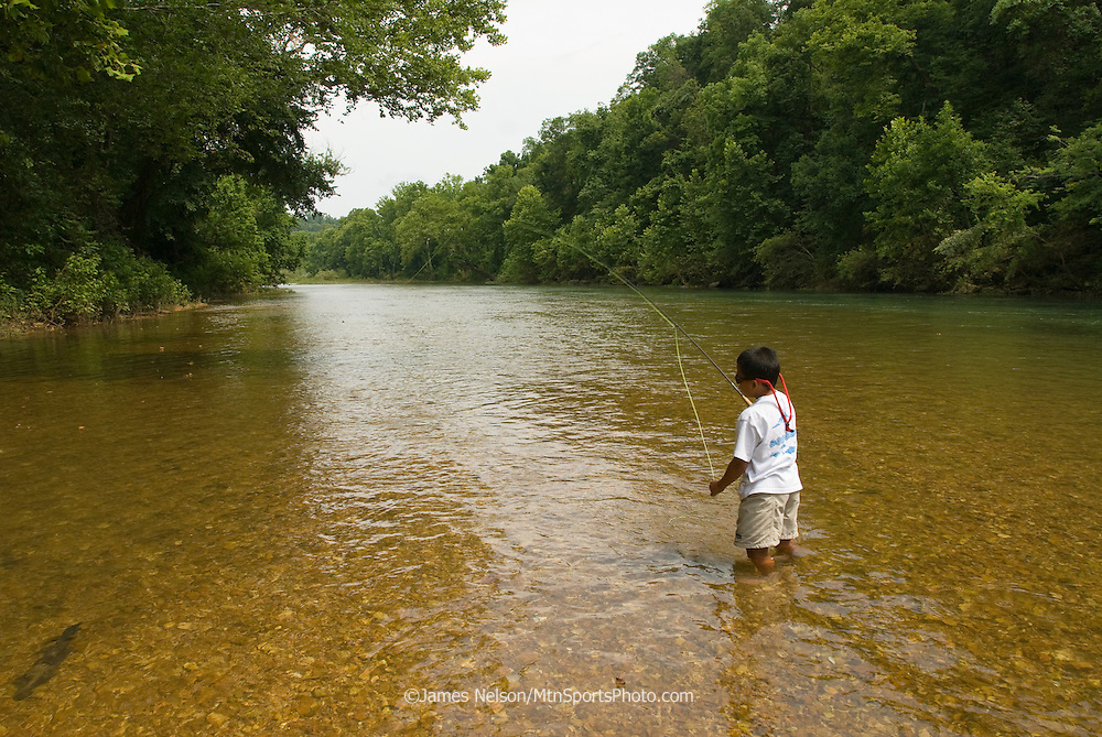 A seven-year-old boy fly fishes for bluegill on the James River, Missouri.