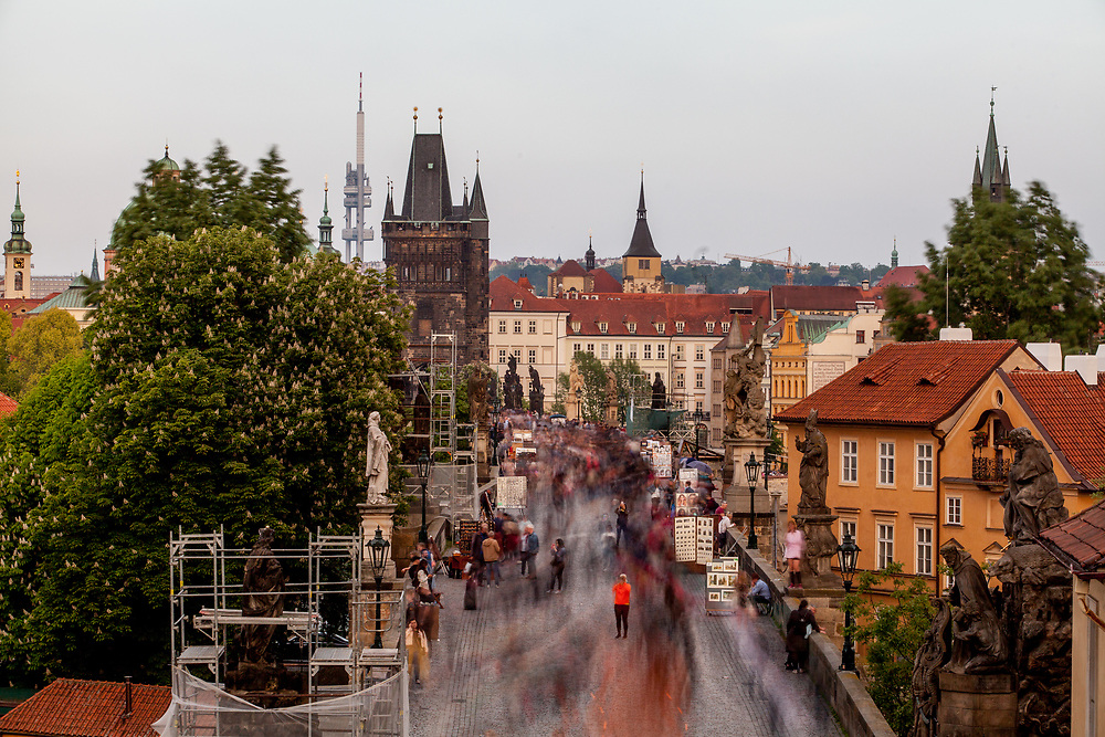 Crowds are moving across Charles Bridge seen from the Lesser Town (Mala Strana) Bridge Towers towards the city center.