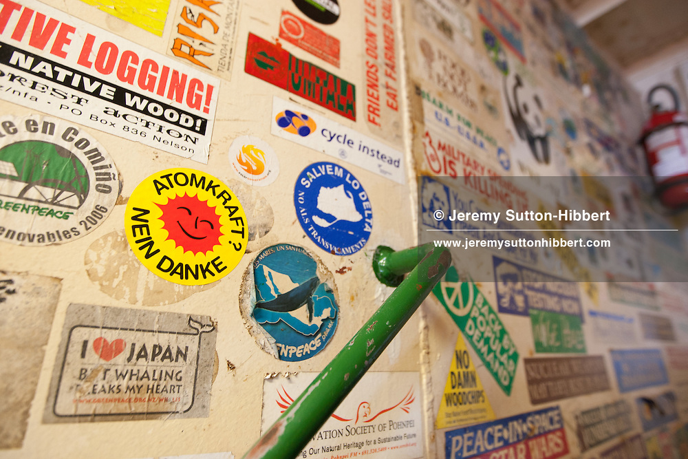 A wall of campaign stickers from various campaigns on board the Greenpeace ship Rainbow Warrior, as it transits northwards to Fukushima, Japan, on Monday 25th April 2011.