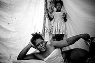 A woman with an injured leg lies in her tent in a camp for those displaced by the recent earthquake in Petionville, outside Port-au-Prince, Haiti.