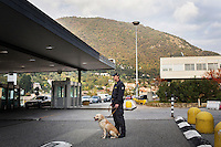 COMO, ITALY - 25 October 2013: A Dog unit of Italy's Guardia di Finanza (Financial Police) waits together with his cash dog for a call from his colleagues to inspect cars suspected of carrying undeclared cash into Switzerland in Como, Italy, at the border with Chiasso (Switzerland) on October 25th 2013. Cash dogs are sniffer dogs that have specially trained to detect the ink on currency notes. In the effort of cracking down on tax evasion and cash smuggling, the Guardia di Finanza works with highly trained dogs in outposts along its borders with Switzerland and France, and in international airports such as Rome Fiumicino and Milano Malpensa.<br /> <br /> In Italy, the law allows to travel with up to 10,000 euros in cash. Beyond that, one must declare to the authorities.<br /> <br /> In 2012, the Guardia di Finanza of the  borders with Chiasso in Switzerland have intercepted more than 55 million euros not declared. In 2013, until September 31st, they have intercepted more than 92 million euros.  The Guardia di Finanza of the Chiasso outpost has been using cash dogs since 2010.