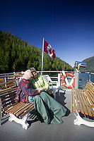 Two elderly friends huddle together for warmth while reading atop the deck of the MV Uchuck III enroute to Friendly Cove on Western Vancouver Island.  British Columbia, Canada.