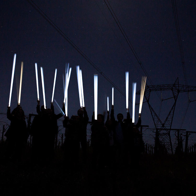 "Expropriated farmers and memebers of the ""no-power line"" committee prove the existence of a strong electromagnetic radiation under the wires of a power line. Because of the Tesla effect, neon tubes will ignite spontaneously in the proximity of the high-tension wires. The mega power line that the company TERNA plans to build will have a much greater extent, equal to 380kv, distributed over 19 cables and hundreds of single pole pylons up to 70 meters high."