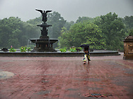 A lady runs for shelter after Bethesda, the Angel of the Water, does her magic; Central Park.