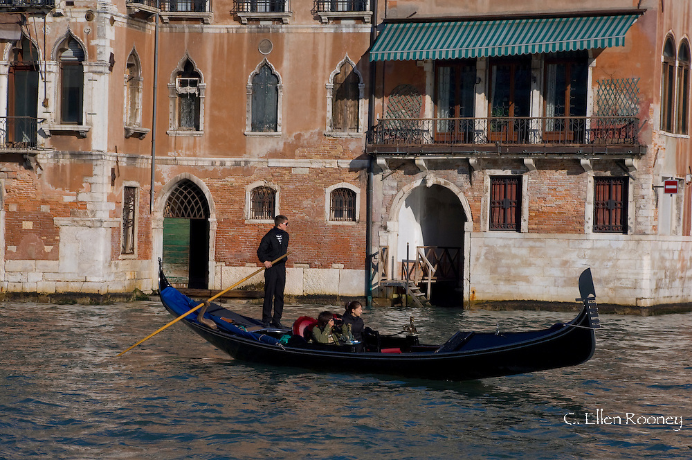 A gondola carrying a pair of tourists on The Grand Canal, Venice, Italy