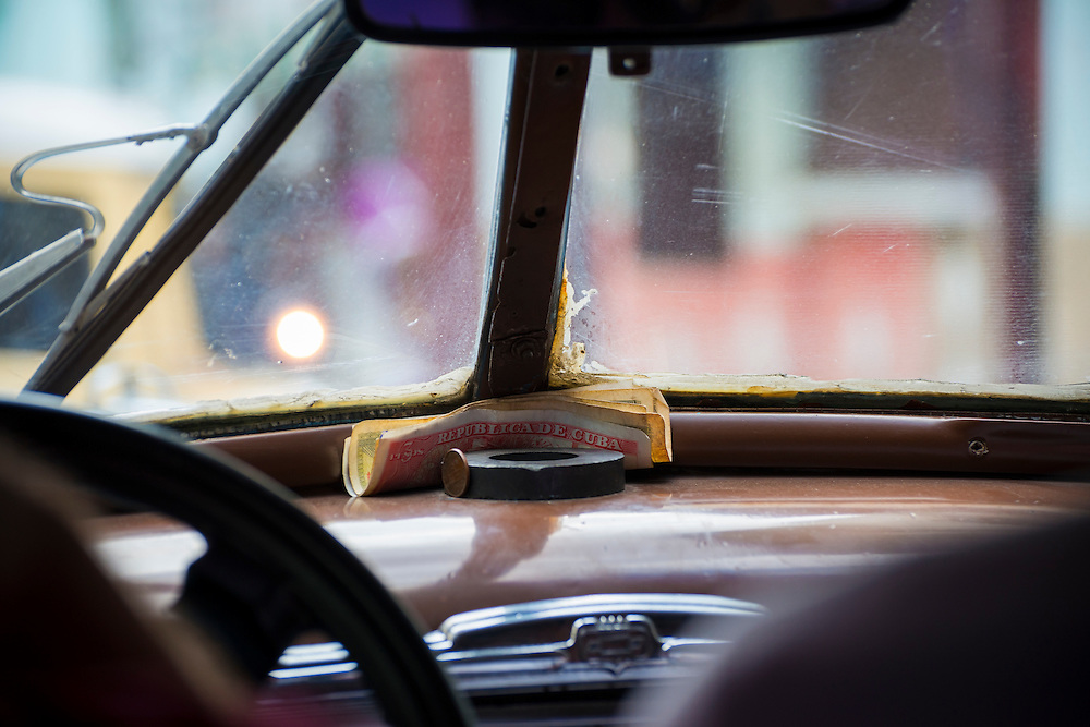 Cuban notes are tucked into the dashboard of an old 1950s-era Chevrolet used today as a taxi in Havana, Cuba.