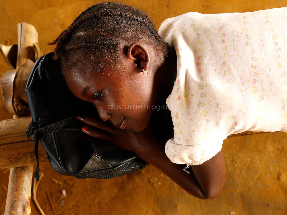 A pupil rests on a bench at J.S. Varfley School, Kingsville #7, Liberia.