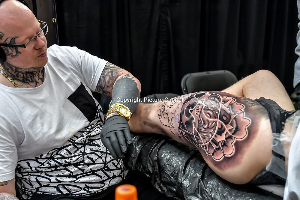 Patryk Mazur, tattoo a client at The Great British Tattoo Show, on 26 May 2019, London, UK.