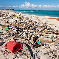 Dutch Antilles, Aruba, Trash covers sandy beach along Caribbean shoreline