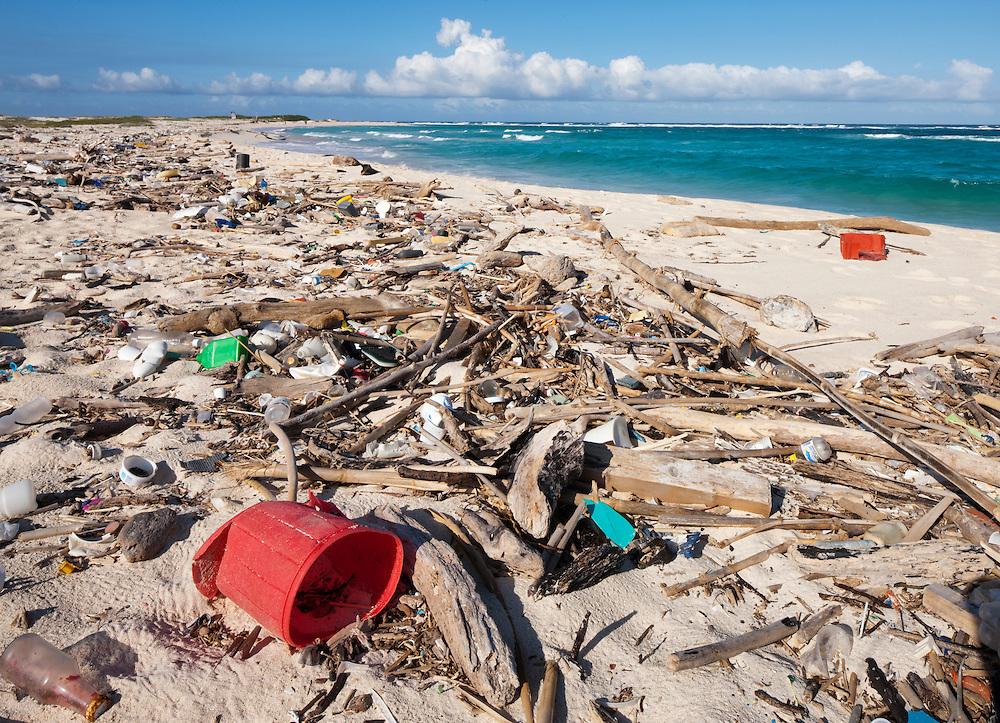 Dutch Antilles, Aruba, Trash covers sandy beach along Caribbean shoreline